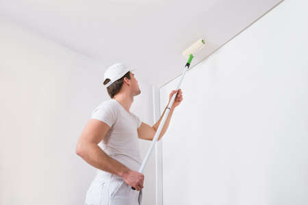 Photo for Young Painter In White Uniform Painting With Paint Roller On Wall - Royalty Free Image