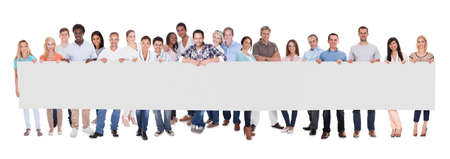 Photo for Group of stylish professional business people standing in a line holding up a long blank banner for your advertising or text - Royalty Free Image