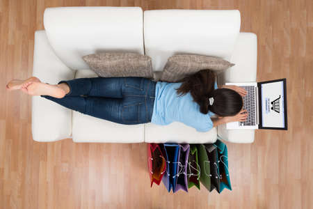 Photo for High Angle View Of Young Happy Woman On Sofa Shopping Online With Laptop - Royalty Free Image