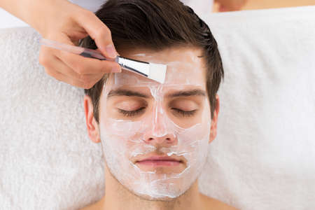 Photo for Therapist Hands With Brush Applying Face Mask To A Young Man In A Spa - Royalty Free Image