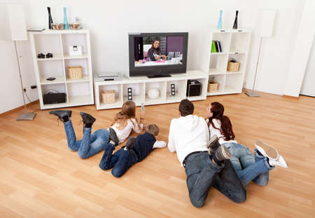 Photo pour Young family watching TV together at home - image libre de droit
