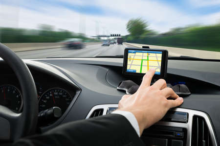 Photo pour Close-up Of A Person's Hand Using Gps Navigation System In Car - image libre de droit