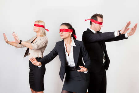 Photo pour Group of disoriented businesspeople with red ribbons on eyes - image libre de droit