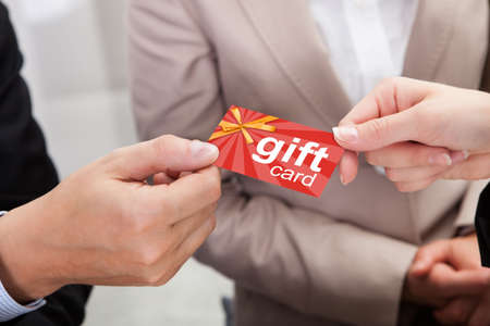 Photo pour Close-up Of Businessperson Hands Giving Gift Card To Other Businessperson - image libre de droit