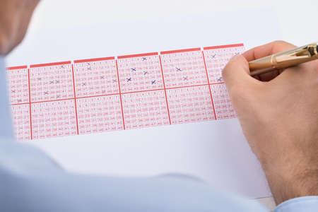 Foto de Close-up Of Businessperson Marking On Lottery Ticket - Imagen libre de derechos