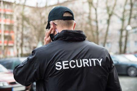 Foto de Security Guard In Black Uniform Listening With Earpiece - Imagen libre de derechos