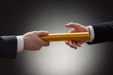 Photo for Close-up Of Two Businessman's Hand Passing A Golden Relay Baton - Royalty Free Image