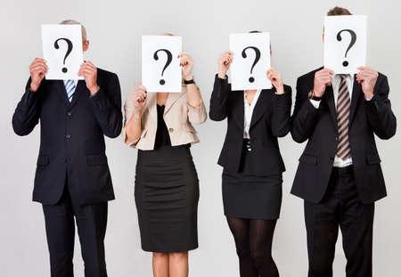 Photo pour Group of unidentifiable business people hiding under question marks - image libre de droit
