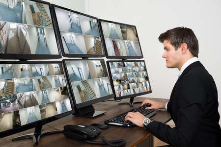 Foto de Young Male Operator Looking At Multiple Camera Footage On Computers - Imagen libre de derechos