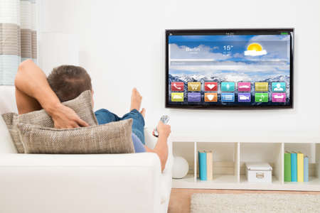 Foto de Young Man Lying On Sofa Using Remote Control In Front Of Television - Imagen libre de derechos