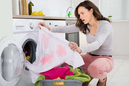 Photo pour Shock Young Woman Looking At Stained Cloth In Kitchen - image libre de droit