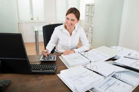Photo pour Happy Businesswoman Calculating Financial Data With Calculator At Desk - image libre de droit