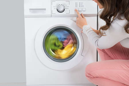 Foto per Close-up Of Young Woman Pressing Button Of Washing Machine In Kitchen - Immagine Royalty Free