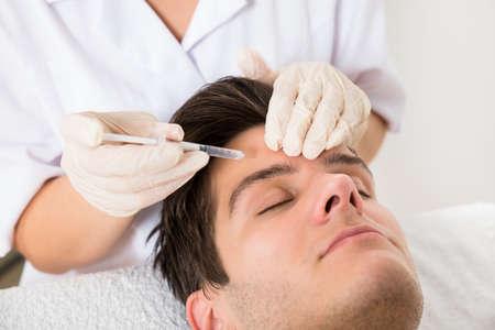 Photo pour Young Man Having Botox Treatment At Beauty Clinic - image libre de droit
