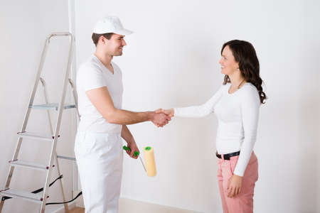 Photo for Young Beautiful Woman Shaking Hands To Painter With Paint Roller At Home - Royalty Free Image