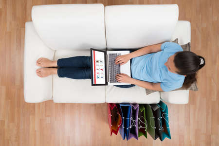 Photo pour Woman On Sofa With Shopping Bags Browsing Shopping Site On Laptop - image libre de droit