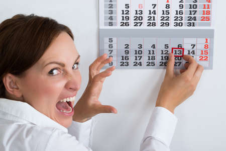 Photo for Close-up Of Frightening Businesswoman Marking Friday 13 On Calendar - Royalty Free Image