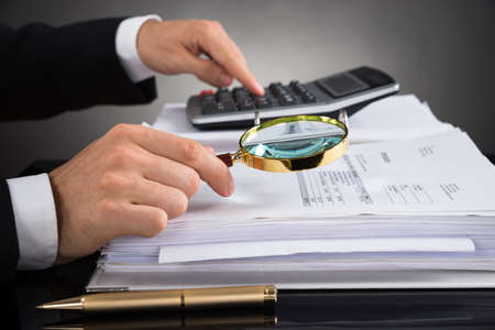 Photo pour Close-up Of Businessperson Hands Checking Invoice With Magnifying Glass At Desk - image libre de droit