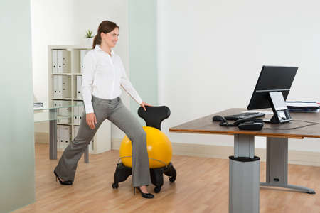 Photo pour Young Happy Businesswoman Exercising With Pilates Ball On Chair In Office - image libre de droit