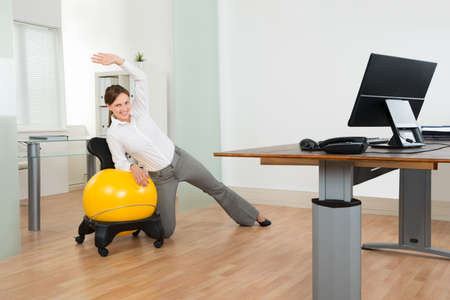Foto de Young Happy Businesswoman Doing Fitness Exercise On Yellow Pilates Ball In Office - Imagen libre de derechos
