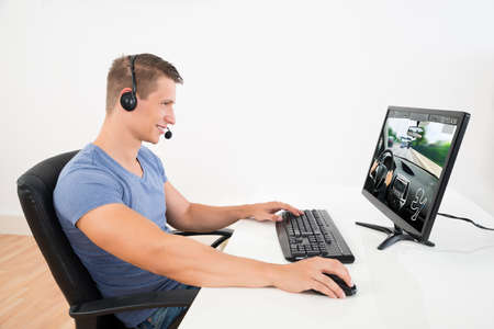 Photo pour Happy Man With Headset Playing Game On Desktop Computer At Home - image libre de droit