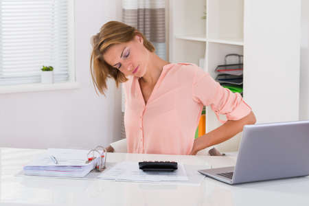 Photo for Young Woman Suffering From Backache While Calculating Tax At Desk - Royalty Free Image