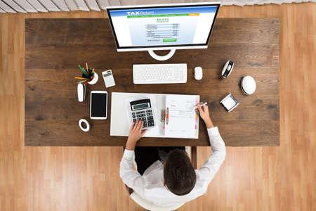 Foto de High Angle View Of Young Businessman Calculating Tax With Computer At Desk - Imagen libre de derechos
