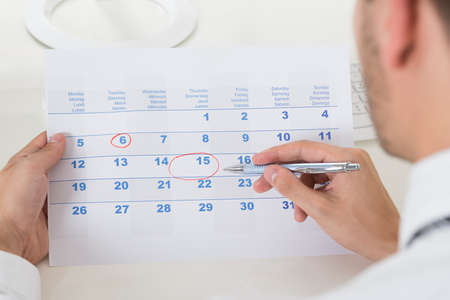Photo for Close-up Of Businessman Hands Marking Date On Calendar - Royalty Free Image