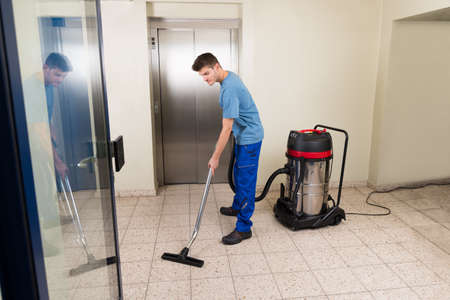 Photo pour Happy Male Worker Cleaning Floor With Vacuum Cleaner Appliance - image libre de droit