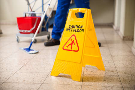 Photo for Low Section Of Worker Mopping Floor With Wet Floor Caution Sign On Floor - Royalty Free Image