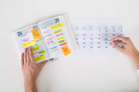 Photo for Close-up Of Person Hands Highlighting Date On Calendar With Diary At Desk - Royalty Free Image