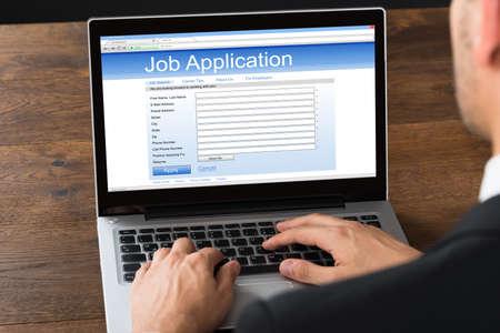 Photo pour Close-up Of Businessman Filling Online Job Application Form On Laptop - image libre de droit