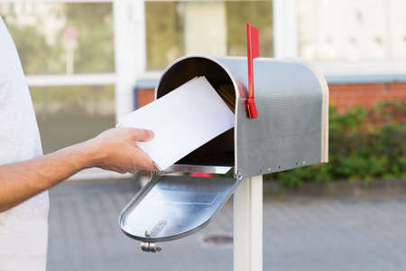 Foto de Close-up Of Person Putting Stack Of Letters In Mailbox - Imagen libre de derechos
