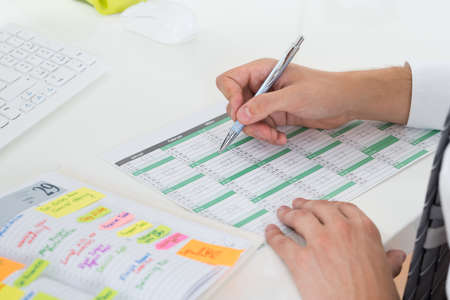 Photo for Close-up Of Businessman With Calendar Writing Schedule In Diary - Royalty Free Image