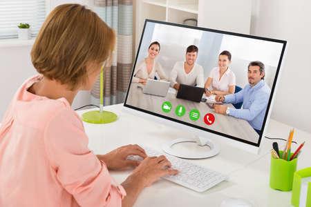 Foto de Young Woman Videoconferencing With Colleagues On Computer At Desk - Imagen libre de derechos