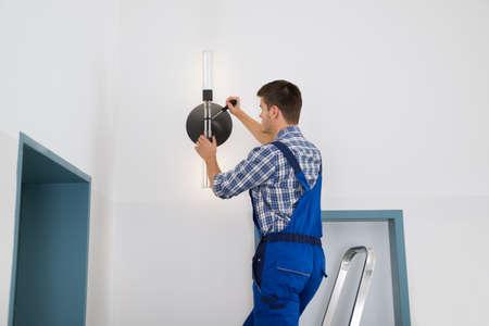 Foto de Male Electrician Standing On Stepladder Repairing Light - Imagen libre de derechos