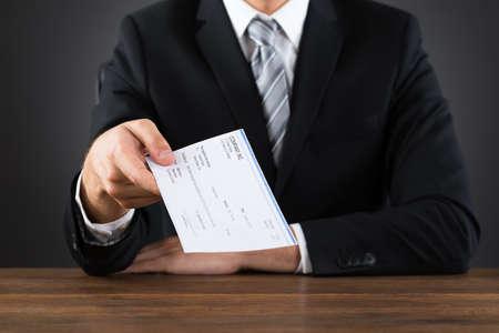 Foto de Close-up Of Businessperson Giving Cheque At Wooden Desk - Imagen libre de derechos