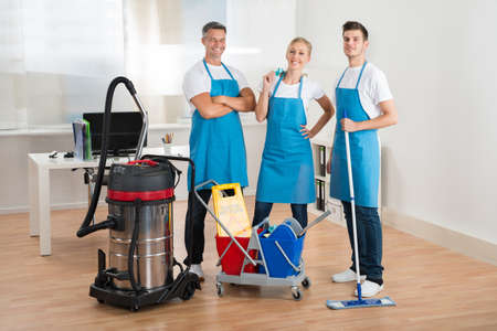 Photo pour Happy Janitors With Vacuum Cleaner And Cleaning Equipments In Office - image libre de droit