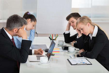 Foto de Team Of Unhappy Businesspeople Sitting In Business Meeting - Imagen libre de derechos