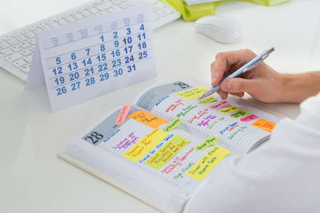 Photo pour Close-up Of Businessman With Calendar Writing Schedule In Diary - image libre de droit