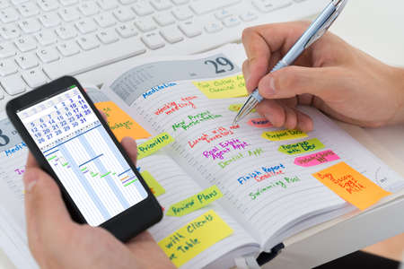 Photo pour Close-up Of Person Hands With Mobile Phone And List Of Work In Diary - image libre de droit
