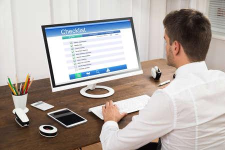 Photo pour Young Businessman Filling Checklist Form On Computer At Wooden Desk - image libre de droit