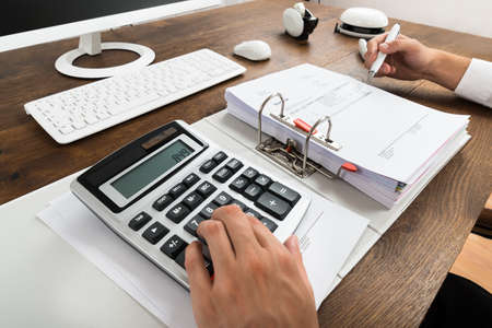 Photo pour Close-up Of Businessman Checking Invoice With Calculator At Desk - image libre de droit
