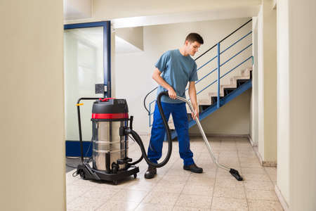 Photo pour Happy Male Worker Cleaning Floor With Vacuum Cleaner Appliance - image libre de droit