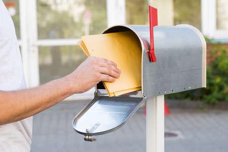 Foto de Close-up Of Person Removing Yellow Letters From Mailbox - Imagen libre de derechos