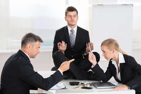 Foto de Two Businesspeople Quarreling In Front Of Businessman Meditating At Desk - Imagen libre de derechos