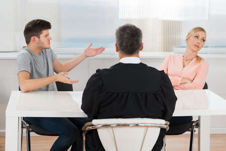 Photo for Rear View Of Judge Sitting In Front Of A Young Couple Having Conflict In Court - Royalty Free Image