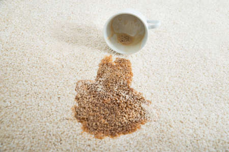 Photo pour Close-up of coffee spilling from cup on carpet - image libre de droit