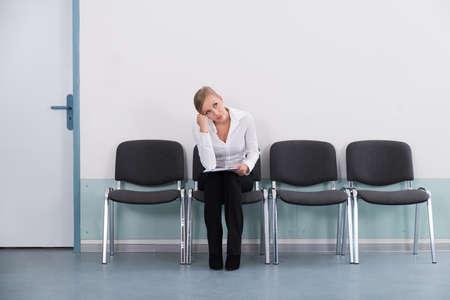 Foto de Young Businesswoman Daydreaming While Sitting On Chair - Imagen libre de derechos