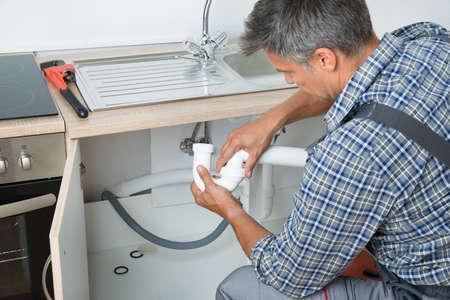 Foto de Side view of mature plumber fixing sink pipe in kitchen - Imagen libre de derechos